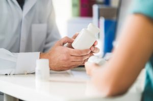 Doctor consulting patient about right medication. Physician holding medicine and pills in hand. Pharmacist in pharmacy in customer service. Pain killers, antidepressants or prescription drugs.