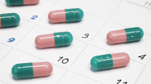 Pick and Green Pills sitting on each calendar day