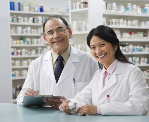 senior pharmacist with his assistant in the drugstore